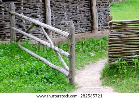 Wicker rustic fence in garden on grass background - stock photo