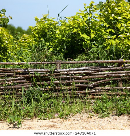 wicker rustic fence in the summer garden on grass background. - stock photo