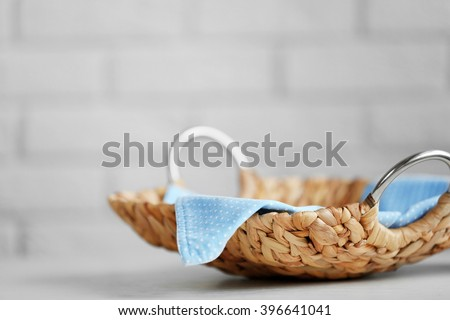 Wicker salver with blue napkin on wooden table background, closeup - stock photo