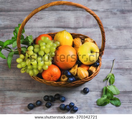 Wicker straw basket with an assortment of fruits and lemon, orange, grape, strawberry, berries Physalis, tangerine on a wooden table in a rustic style, top view - stock photo