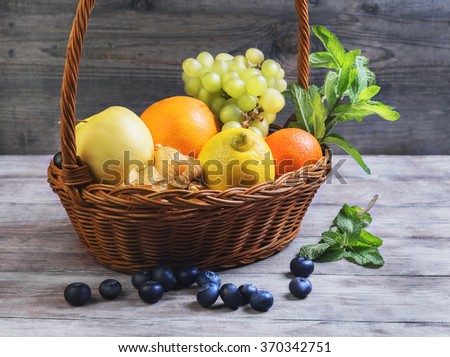 Wicker straw basket with an assortment of fruits and lemon, orange, grape, strawberry, berries Physalis, tangerine on a wooden table in a rustic style - stock photo