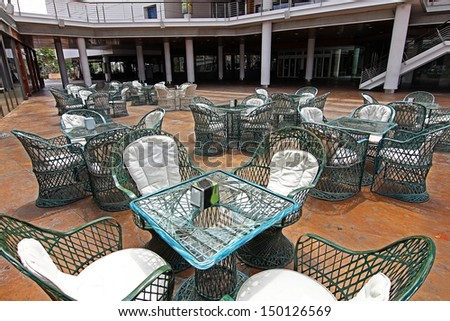 wicker tables and chairs in green - stock photo