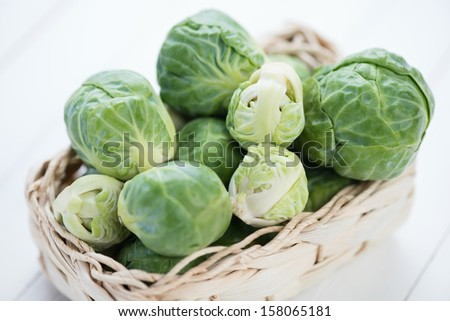 Wicker tray with fresh brussels, close-up, studio shot - stock photo