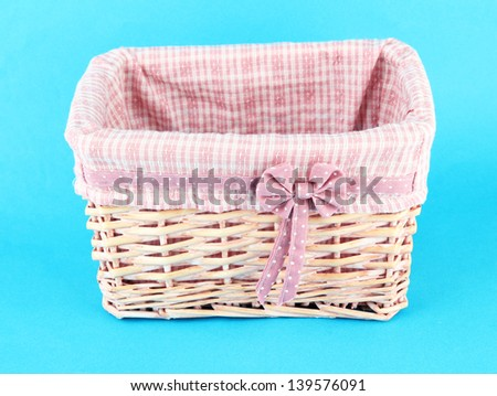 Wicket basket with pink fabric and bow, on color background