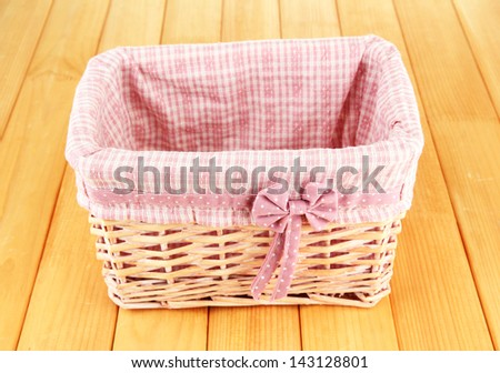 Wicket basket with pink fabric and bow, on wooden background