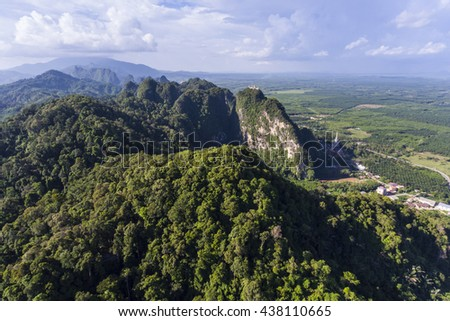 Wide Aerial view of Tiger Cave Temple or Wat Thum Sua at Krabi province, Thailand. At the top of the mountain there is a large golden Buddha statue which is a popular tourist attraction. - stock photo