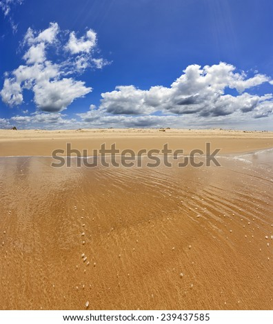 Wide and empty endless pure sand beach from transparent sea wave towards sand dune under summer blue sky with white clouds