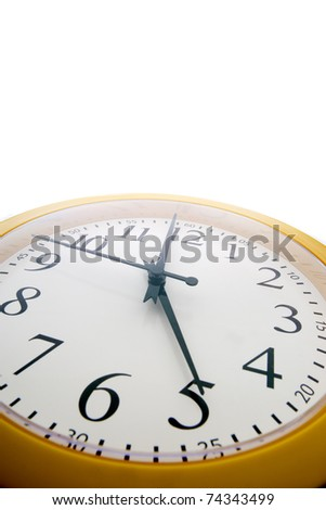 Wide angle close up of an analog clock just before the end of the workday at 5 pm - stock photo