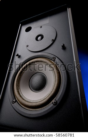 Wide angle close up of an audio loudspeaker with an electric blue glow - stock photo
