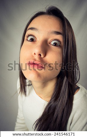 Wide angle distorted funny face of a teenager girl in a kissing expression - stock photo