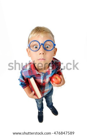 Wide angle full length portrait of boy a student in shirt in glasses hugging book and apple in hands, looking at camera, isolated on white background. School preschool