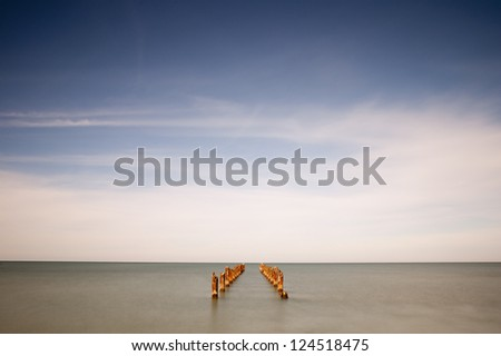 wide angle image of a ruined pier extending to the horizon. long exposure - stock photo