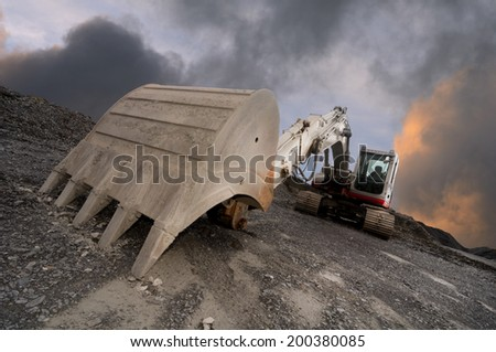 Wide angle image of an excavator in a quarry with a dramatic sky background - stock photo