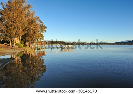wide angle landscape of lake Te Anau in south New Zealand, yellow trees beside the lake