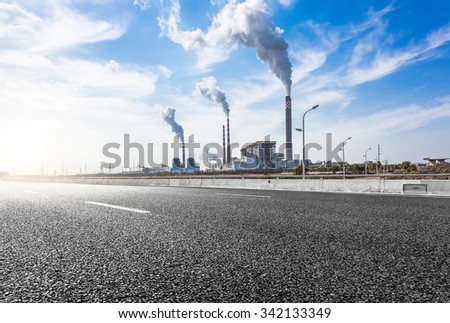 Wide angle landscape photograph of a road leading to a power plant - stock photo