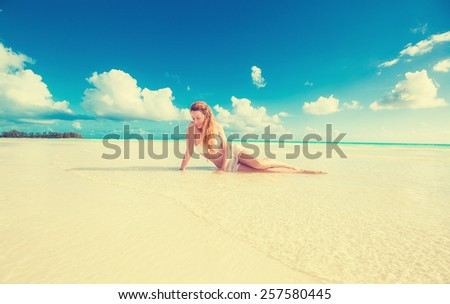 Wide angle landscape picture. Young beautiful smiling woman laying on beach yellow sand with tropical blue sea sky ocean background. Paradise getaway nature destination travel vacation concept - stock photo