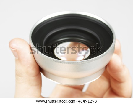 Wide angle lens in a hand on white background - stock photo