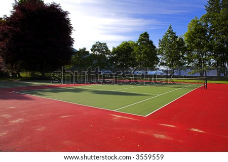 wide angle of colorful tennis court over blue sky - stock photo