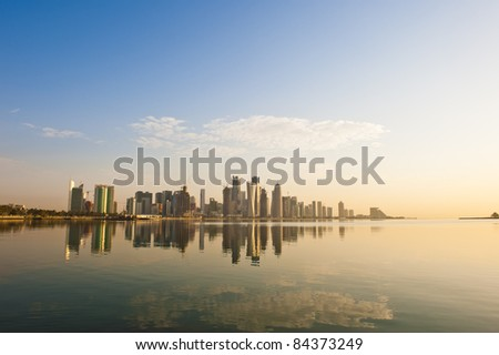Wide angle of Doha, Qatar, where the skyline changed drastically over the past 5 years. Image captured early in the morning with the sun rising from the right and some rare fluffy clouds in the sky.. - stock photo