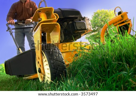Wide angle of lawnmower cutting overgrown grass.