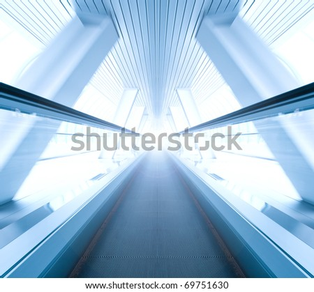 wide angle of moving blue escalator inside contemporary airport - stock photo