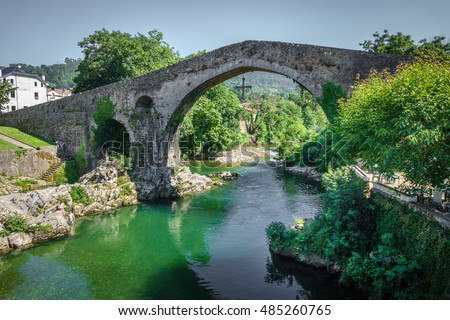 Wide angle of old Roman stone bridge with cross an river in Cangas de Onis, Asturias, Spain