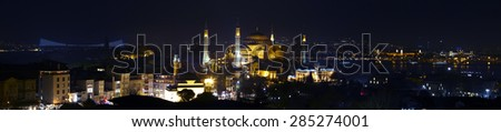 Wide angle panorama of Istanbul old city district at nightlight illumination Including most famous attractions Sophia and Blue Mosque with water of Bosporus and Asian side of town on background - stock photo