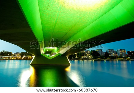 Wide angle perspective of the green bridge reflecting in the river - stock photo