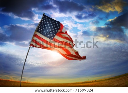 Wide angle photo of a tattered American flag blowing in the wind against a beautiful cloudscape - stock photo