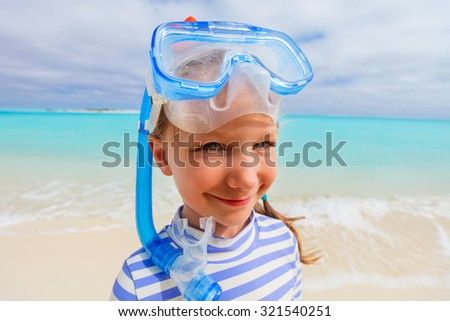 Wide angle photo of adorable little girl with snorkeling equipment at beach during summer vacation - stock photo