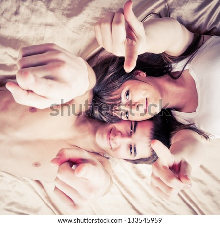 wide angle picture of a young couple pointing to you - stock photo