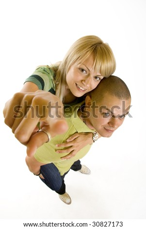 wide angle picture of a young couple pointing to you