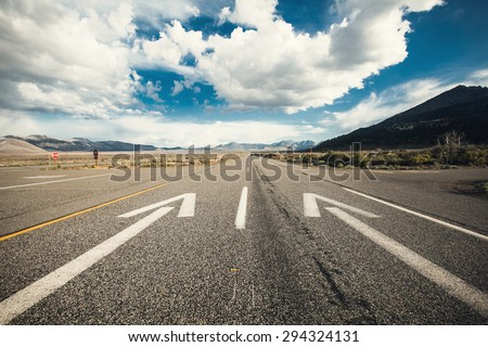 Wide angle picture of driving on an empty road through the beautiful landscape at sunny day. Concept vision for a new beginning with a sign start and an arrow towards the sun. - stock photo