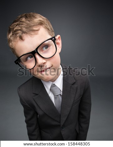 Wide angle portrait of little pensive businessmen in glasses, on grey background. Concept of leadership and success
