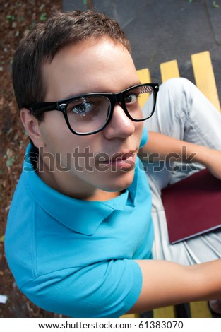wide angle portrait of young man in glasses sitting on a bench - stock photo