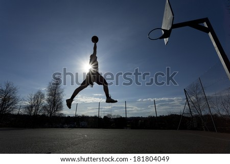 Wide angle shot of a basketball player silhouette in mid air about to slam dunk the ball with the sun creating a flare effect - stock photo