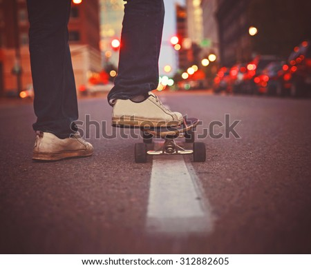 wide angle shot of a guy getting ready to skate down an empty urban street in a dark city toned with a retro vintage instagram filter app or action effect  - stock photo
