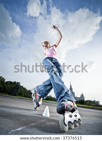 Wide-angle shot of a rollerblading girl performing 'compass' element - little motion blur - stock photo