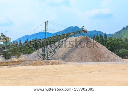 wide angle shot of conveyor and pile of quarry stone for lime industry against white cloud and blue sky - stock photo