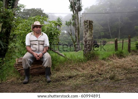 Wide angle shot of Costa Rican ranch hand by the side of the road - stock photo