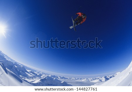 Wide angle shot of skier jumping against blue sky - stock photo