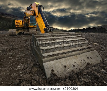 wide angle, threatening view of an excavator with a stormy sky brewing in the distance