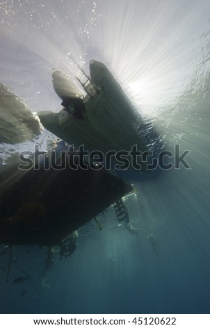 Wide angle underwater view of the hull of a speed boat next to a floating jetty. Red Sea, Egypt.