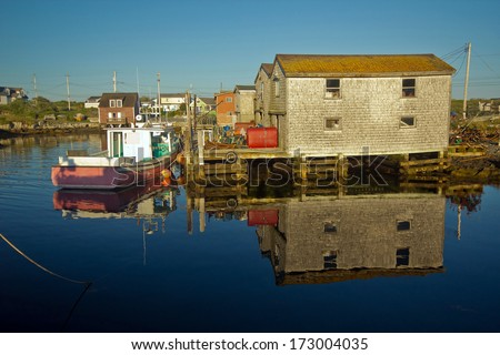 Wide angle view at sunset,of colorful boats and fishing shacks and reflections in the water at the world famous,tranquil,quaint,fishing village of Peggy's Cove,Nova Scotia,Canada - stock photo