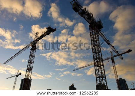 Wide angle view of a construction site with many cranes around late afternoon - stock photo