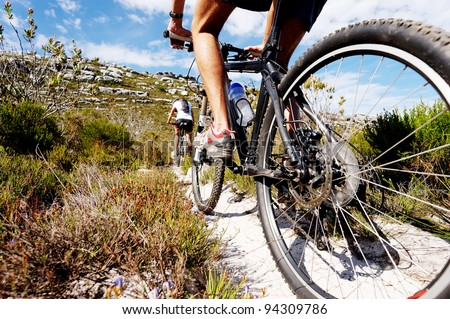 Wide angle view of a cyclist riding a bike on a nature trail in the mountains. two people living a healthy lifestyle - stock photo