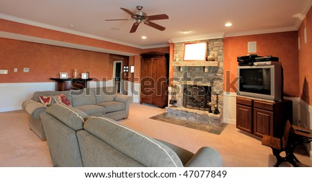 Wide angle view of a family room, with ceiling fan, couches, and fireplace. Horizontal format.