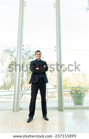 Wide angle view of a friendly Latin businessman standing inside a tall building - stock photo