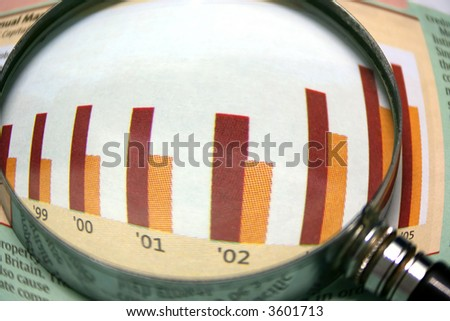 Wide-angle view of a magnifying glass focusing on a graph in the business section of the newspaper. - stock photo