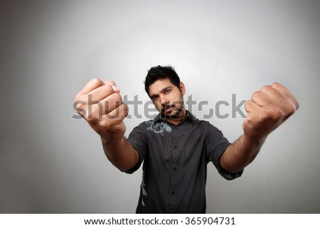Wide angle view of a man showing his closed hands. Selectively focused on the hand
